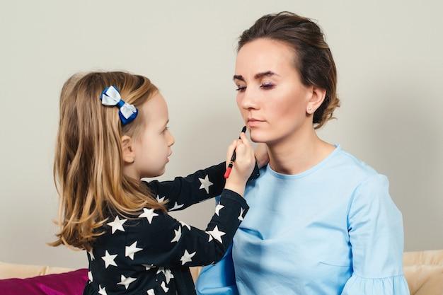 母と娘が化粧をしています。一緒に楽しんでいる素敵なママと子供。母の日おめでとう。健康な子供の化粧品。幸せな愛情のある家族。
