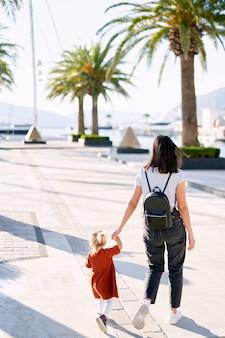 Мать и дочь гуляют среди пальм в гавани.