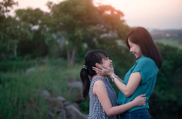 母と娘は、夕日と緑の自然の中で抱き締めて屋外で楽しんでいます