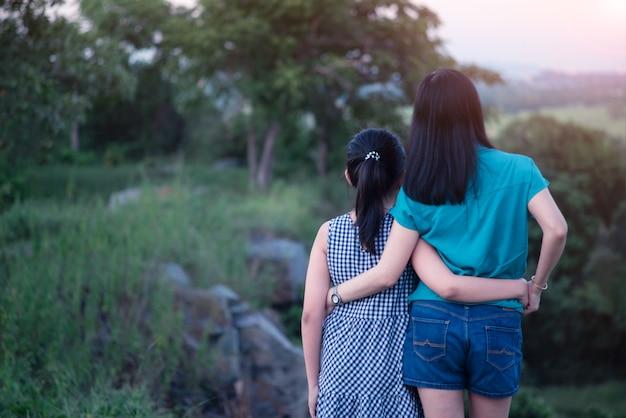 母と娘は夕日と山の頂上に抱き締めて立っています