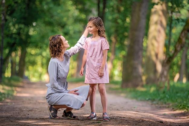 엄마와 딸이 공원에서 껴안고 있습니다. 행복한 가족 개념입니다. 가족 야외 라이프 스타일과 아름다움 자연 장면입니다. 함께 쉬고 있는 행복한 가족. 가족 생활의 행복과 조화.