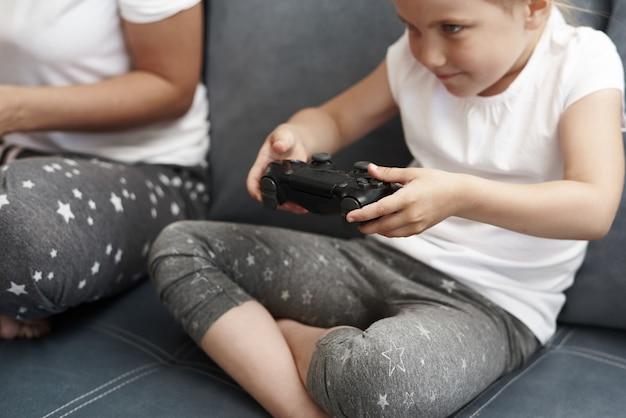 母と娘はコンピューターゲームをプレイしています。小さな女の子がゲームコンソールを遊んでいます。