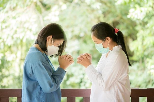 어머니와 딸이 함께 격려하고 지원하기 위해 기도하고 있습니다.