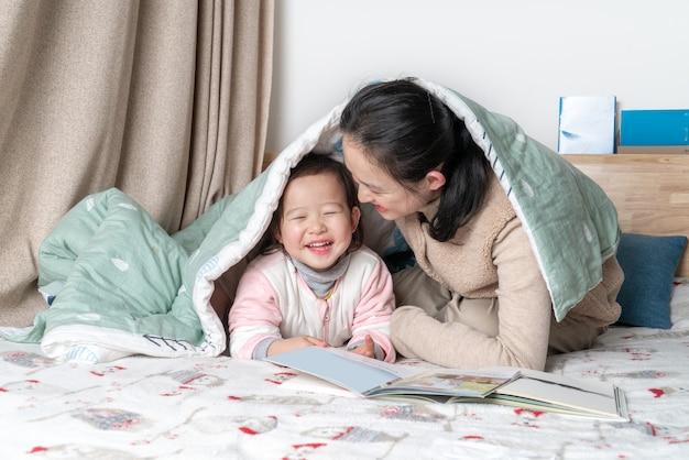 母と娘はベッドで読んでいます