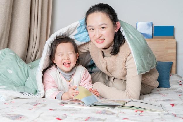 母と娘はベッドで一緒に読んでいます