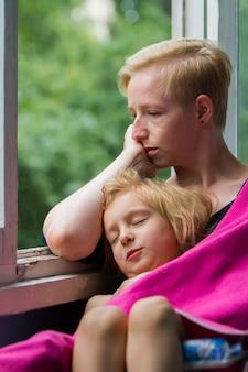 엄마와 딸은 열린 창문 옆에 앉아 있고, 어머니는 잠자는 딸을 담요에 안고 있습니다.