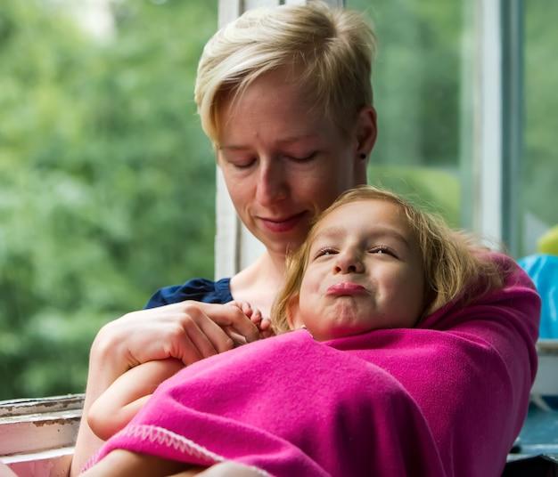 雨が降っている間、母と娘は開いた窓の近くに座っており、子供が感情的になっている瞬間、母は娘を毛布に抱きかかえています。