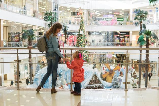 Мать и дочь гуляют и делают покупки в торговом центре