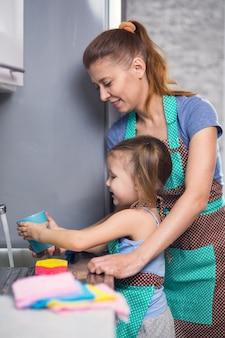 Мать и дочь дома на кухне, мыть посуду вместе