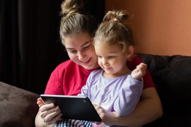 Мать и дочь дома используют планшетный пк