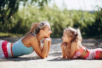 Mother and daughter at the beach practicing yoga
