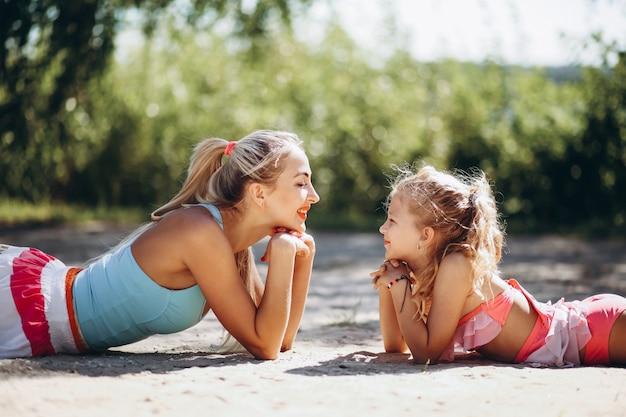 Мать и дочь на пляже, практикующие йогу