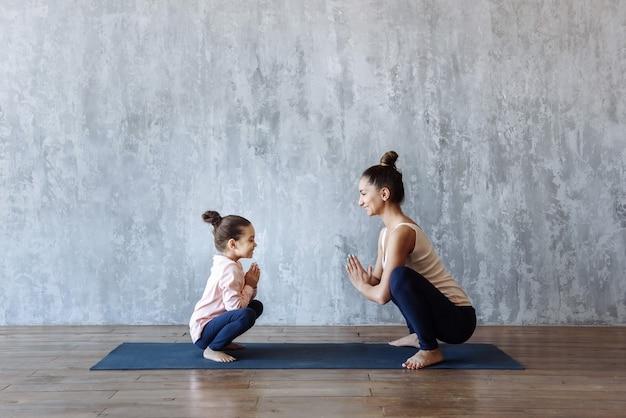 엄마와 딸 아기가 함께 체육관 매트에 요가 연습