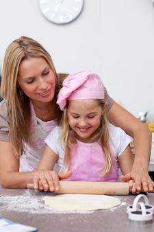 母親と娘はキッチンでビスケットを焼く