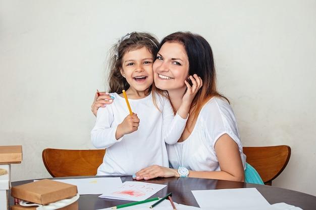 어머니와 딸은 아름답고 행복한 어머니의 날을 위한 카드를 만들고 연필을 함께 앉는다