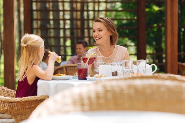 Мать и дочь. красивая счастливая мать и дочь едят вкусные бутерброды на летней террасе