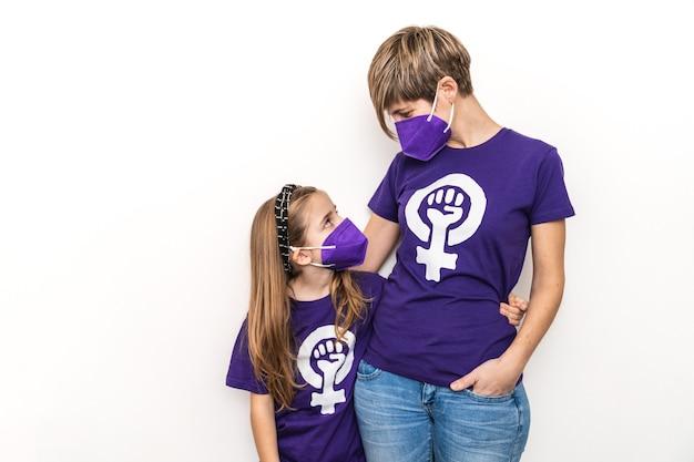 3月8日、白い壁に国際フェミニストの働く女性の日のシンボルが付いた紫色のtシャツを抱き、コロナウイルスのマスクを身に着けている母と娘の金髪