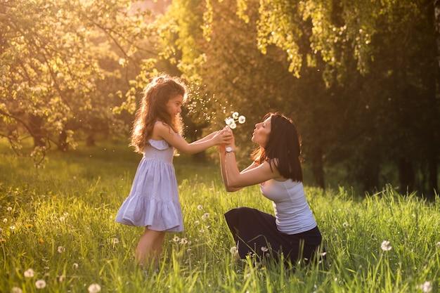 어머니와 딸이 공원에서 민들레 꽃을 불고