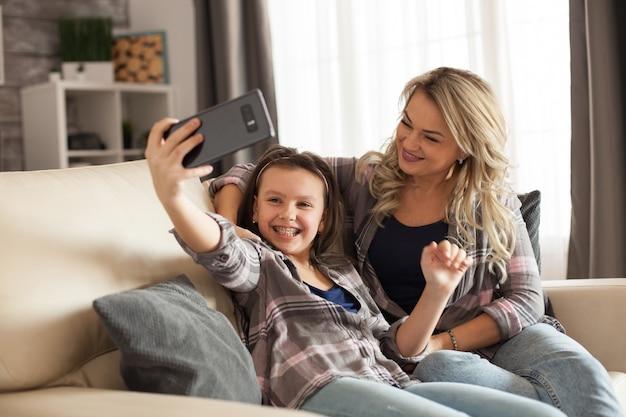 母と娘が自分撮りをして、リビングルームのソファに座って楽しんでいる絆。