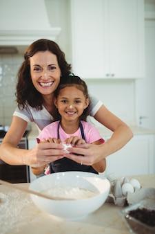 母と娘がクッキーを準備しながらボウルに卵を割る