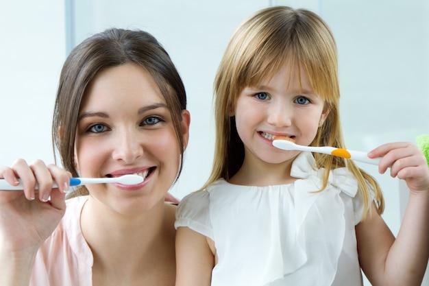 Мать и дочь чистят зубы в ванной комнате