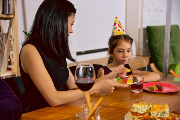 엄마와 딸 집에서 생일을 축하합니다. 큰 가족이 케이크를 먹고 와인을 마시면서 인사하고 아이들을 즐겁게합니다. 축하, 가족, 파티, 가정, 어린 시절, 부모 개념.