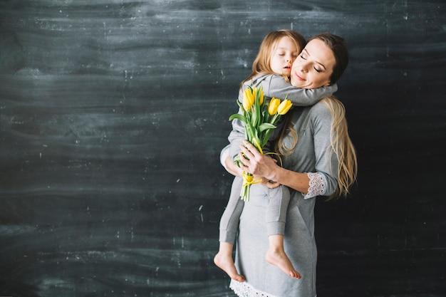 Мать и дочь празднуют день матери с объятием