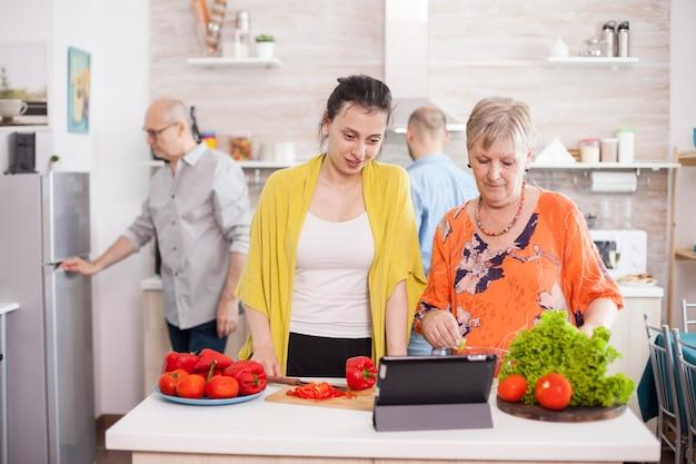 母と娘がキッチンのタブレットpcで野菜サラダのレシピをチェックしています。