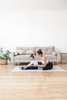 Мать и дочь вместе занимаются спортом дома на ковре, занимаясь растяжкой йоги