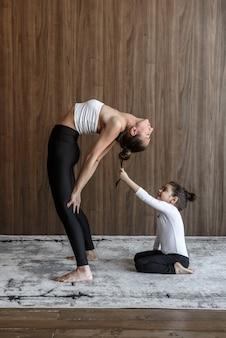Мать и дочь ребенка вместе занимаются спортом йога