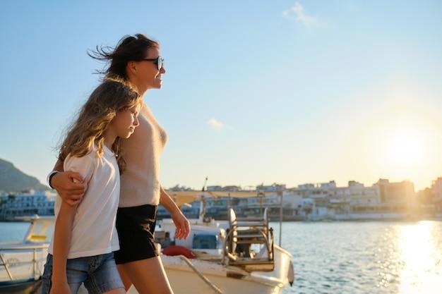 Мать и дочь ребенка обнимаются прогулка на морской пирс