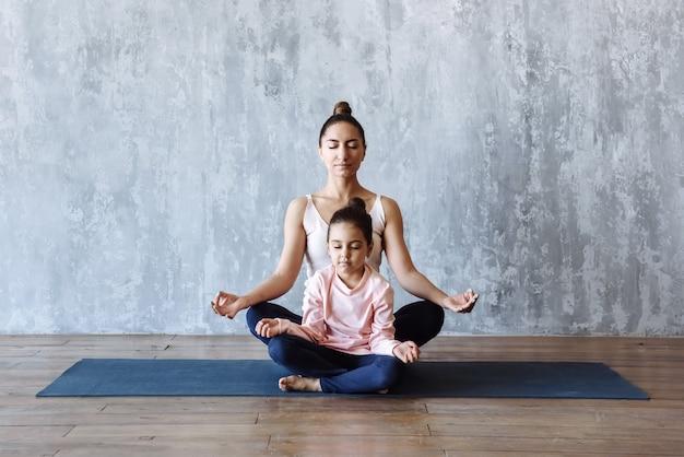Мать и дочь вместе медитируют йогу на коврике на полу