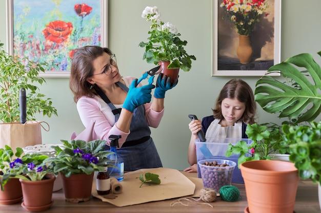 母と娘の子供は鉢植えの植物、花を植えます。趣味とレジャー、ケア、家族、観葉植物、家庭用鉢植えの友達のコンセプト