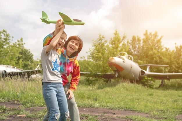 バックグロで本物の飛行機と一緒にフィールドでおもちゃの飛行機で遊んでいる母と娘の子供...