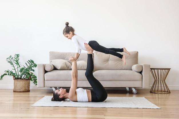 Мать и дочь ребенка вместе практикуют йогу дома возле дивана в гостиной.