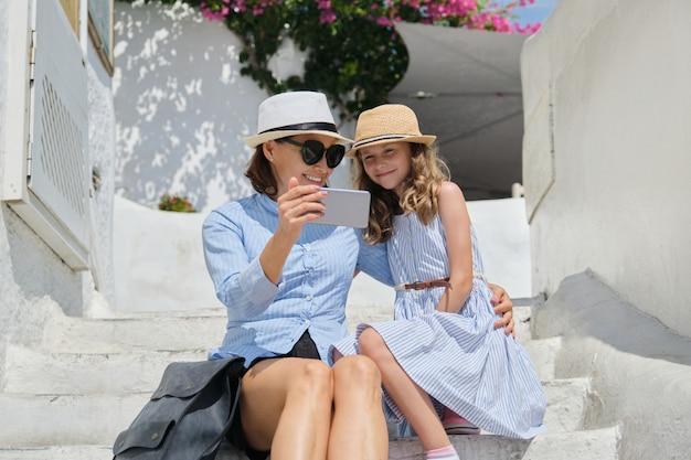 スマートフォンで白い階段に座っている母と娘の子供
