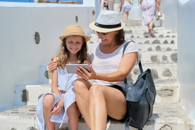 Мать и дочь делают селфи на смартфоне, сидя на белых ступенях средиземноморских городов, летних каникул и семейных путешествий