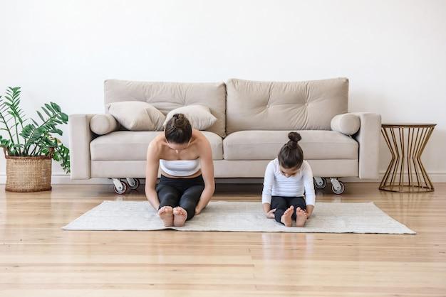 Мать и дочь вместе занимаются спортом дома на ковре, занимаются растяжкой йоги, наклоняясь к ногам
