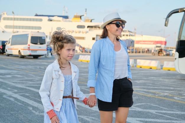 항구를 따라 걷는 엄마와 딸 아이, 가족 바다 여행, 여름 휴가. 바다 교통, 항구 배경에서 페리