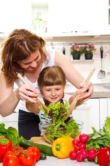 Мать и дочь готовят ужин на кухне