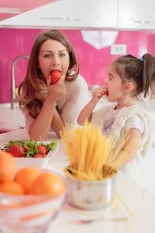 キッチンで料理をする母と娘
