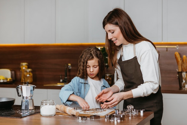 母と娘が自宅のキッチンで一緒に料理をする