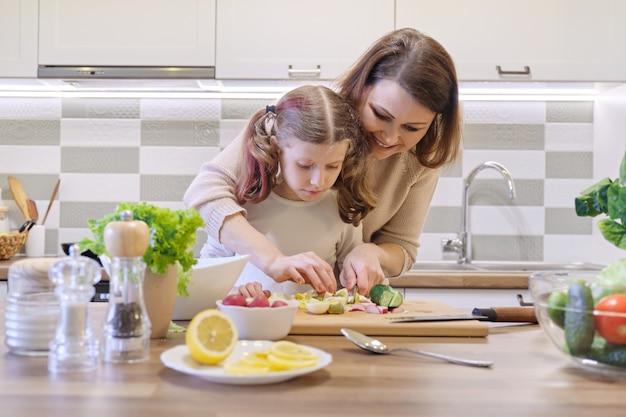 母と娘が一緒にキッチンで料理
