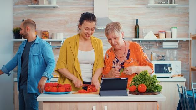 母と娘は、家庭の台所でpcコンピューター上のオンラインレシピを使用して夕食のために野菜を調理します。食事の準備中にデジタルタブレットを使用している女性。拡大家族の居心地の良いリラックスした週末。