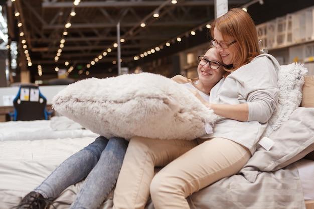 엄마와 딸이 가구점에서 침대에 껴안고 함께 쇼핑을 즐깁니다.