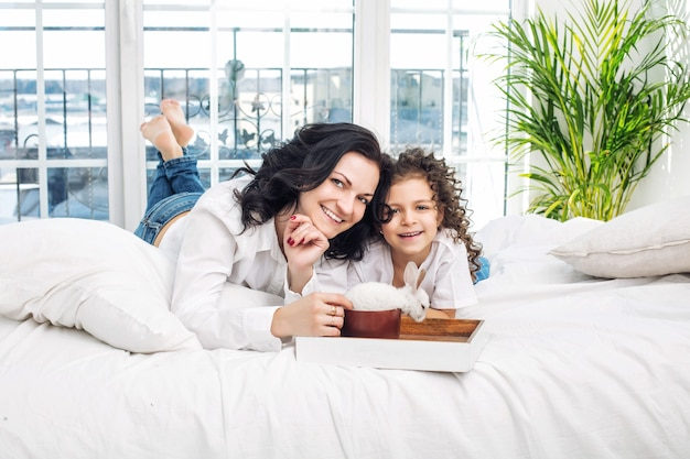 어머니와 딸은 침실에서 쟁반에 흰 토끼와 함께 침대에서 귀엽고 행복합니다