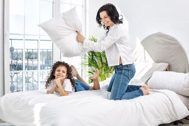 Мать и дочь милые, красивые и счастливые на кровати в спальне дома вместе