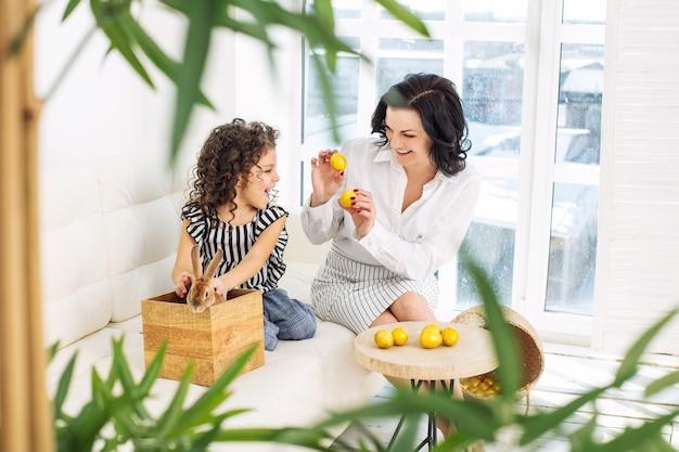 Мать и дочь милые, красивые и счастливые с кроликами и пасхальными яйцами дома вместе