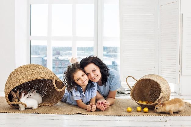 Мать и дочь милые, красивые и счастливые с кроликами и пасхальными яйцами в плетеных корзинах вместе