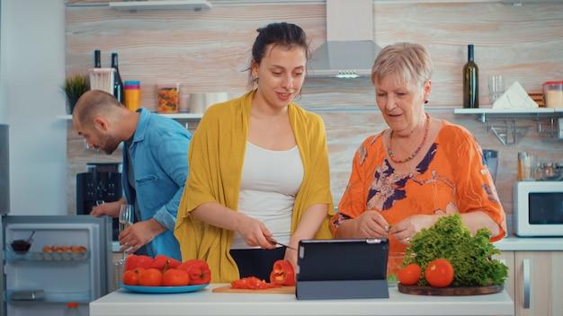 母と娘はコショウを切ってタブレットを見て、家庭の台所のpcコンピューターでオンラインデジタルタブレットレシピを使用して料理をします。食事の準備をしながら。拡大家族の居心地の良いリラックスした週末